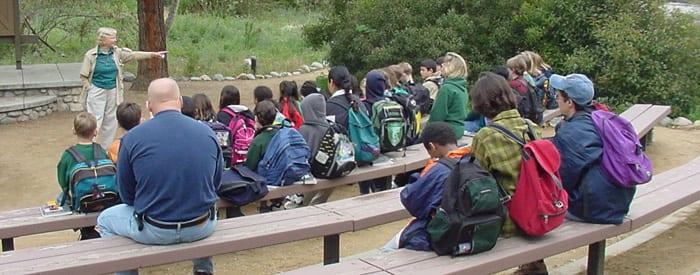 LA County volunteer speaking to group of children