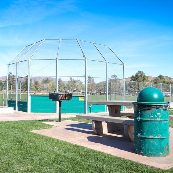 Picnic table, BBQ grill and trash can behind a baseball net
