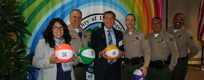 Park and Recs director at an event with multiple sheriffs holding beach balls
