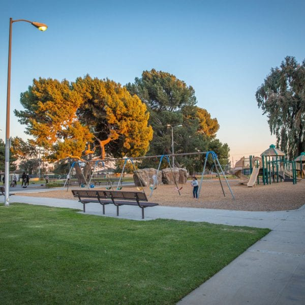 Benches, swings, playground, basketball court and trees