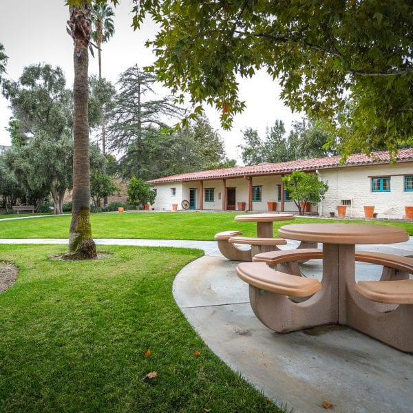 Adobe picnic tables on walkway through lawn