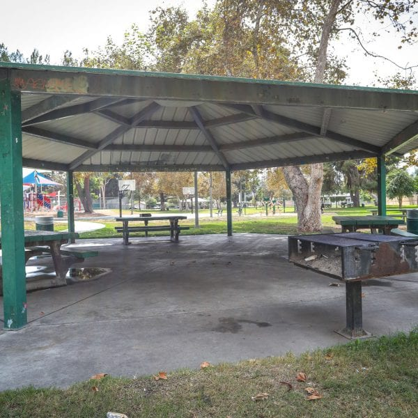 Picnic tables and BBQ grills under an awning