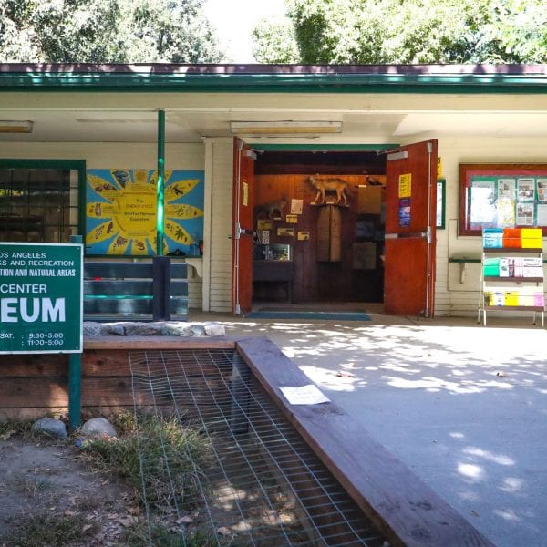Nature center museum, exterior view, showing planter and signs