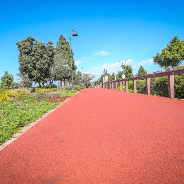 Red exercise track running along a garden and fence