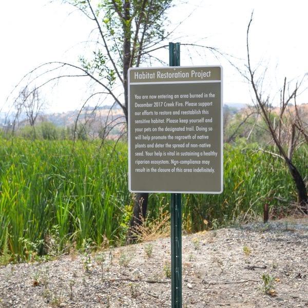 Habitat Restoration Project sign amongst the tall grass