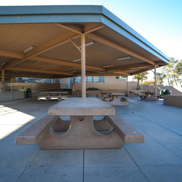 Picnic tables under an awning near a facility