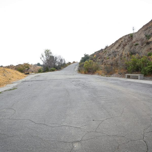 Paved road on hill. Bench and sign to the right