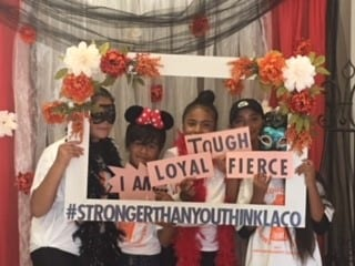 Girls holding up a sign, which reads: I am loyal, tough, fierce. #strongerthanyouthinklaco