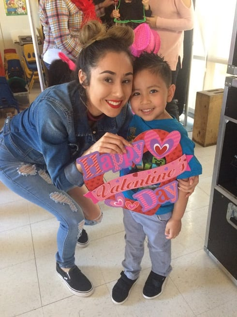 Young woman and boy holding a Happy Valentines Day sign.
