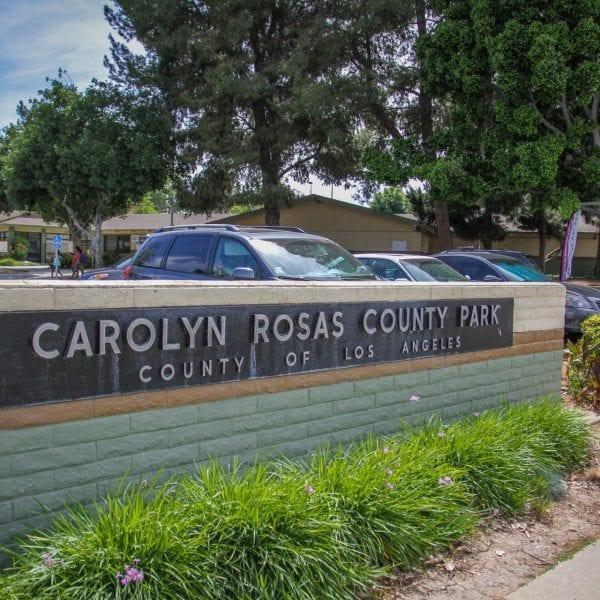 Carolyn Rosas Park sign, cars parked behind