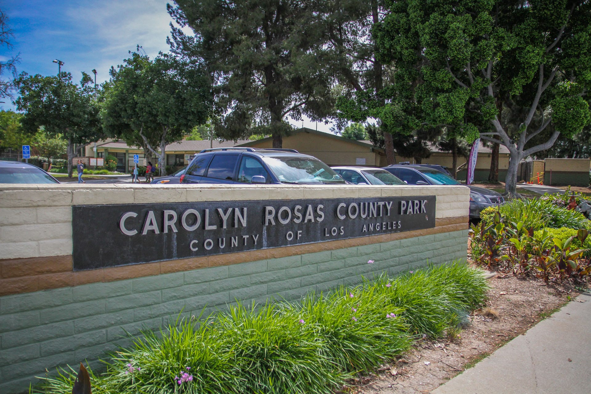 Carolyn Rosas Park sign, cars parked behind