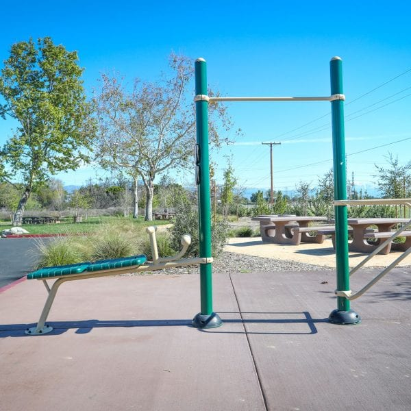 Exercise equipment in front of some picnic tables
