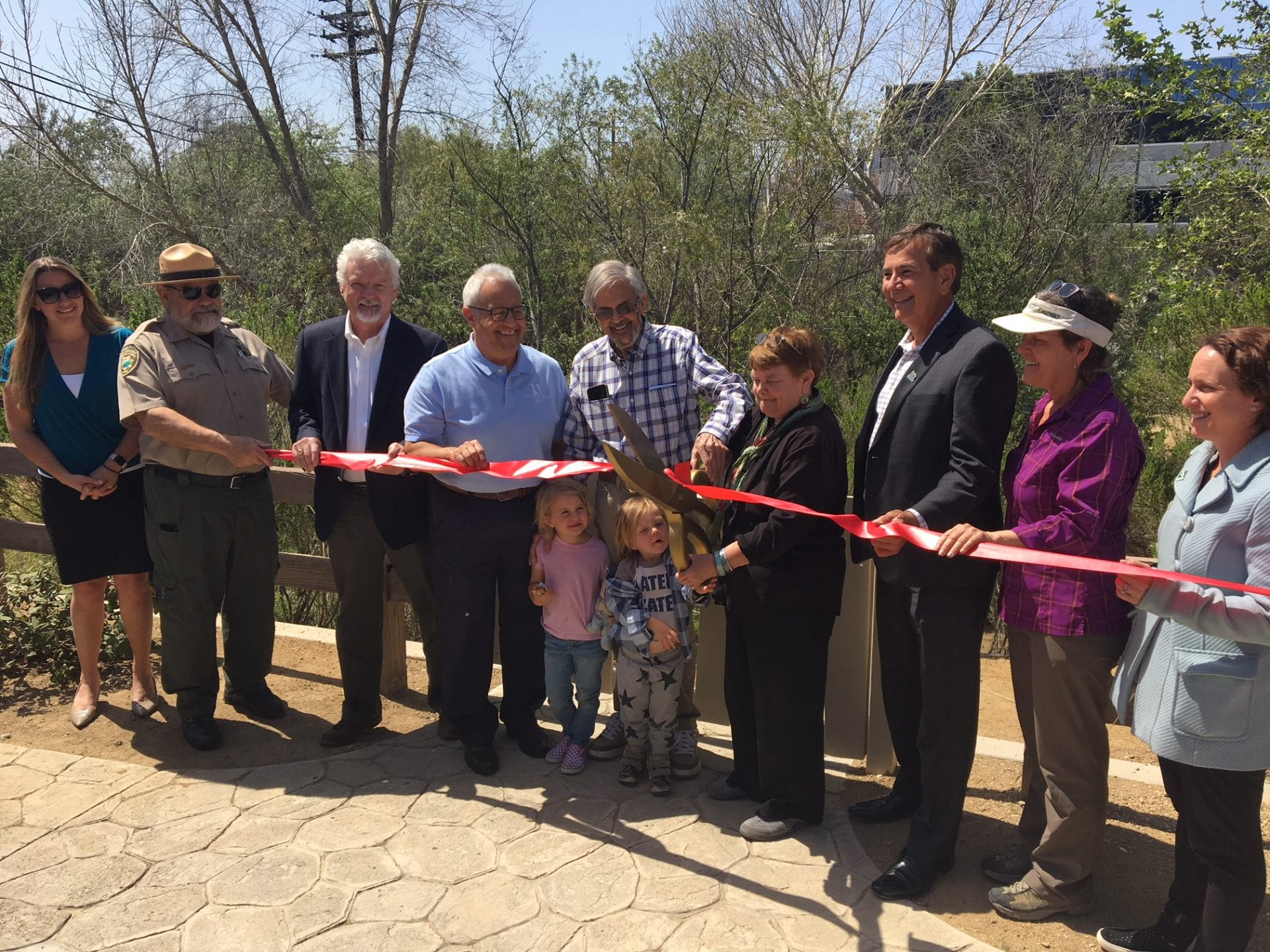 A picture of OHV grand opening with the ribbon cutting and people.