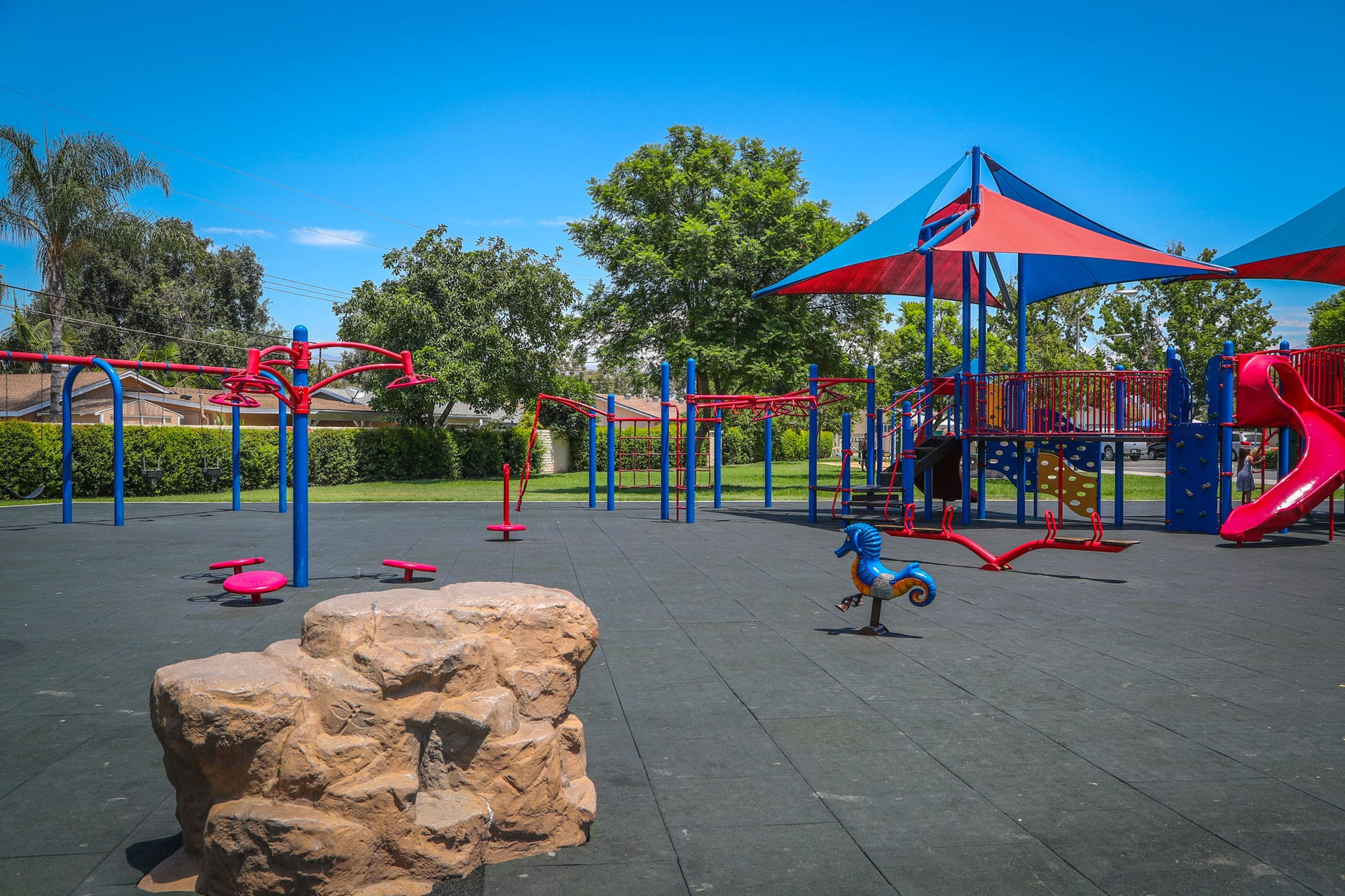 Playground with a small rock structure and jungle gym