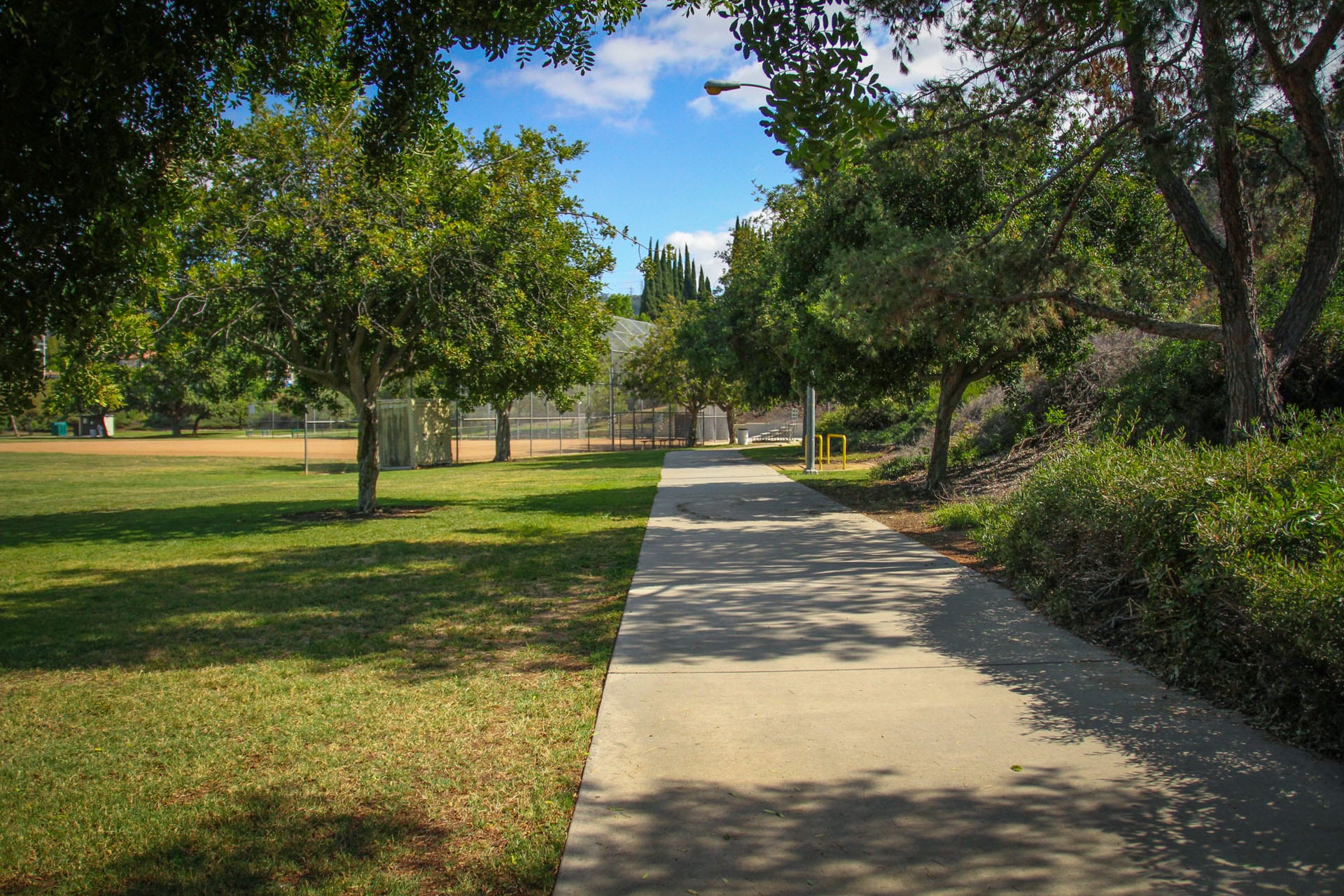 Paved walkway running behind baseball field