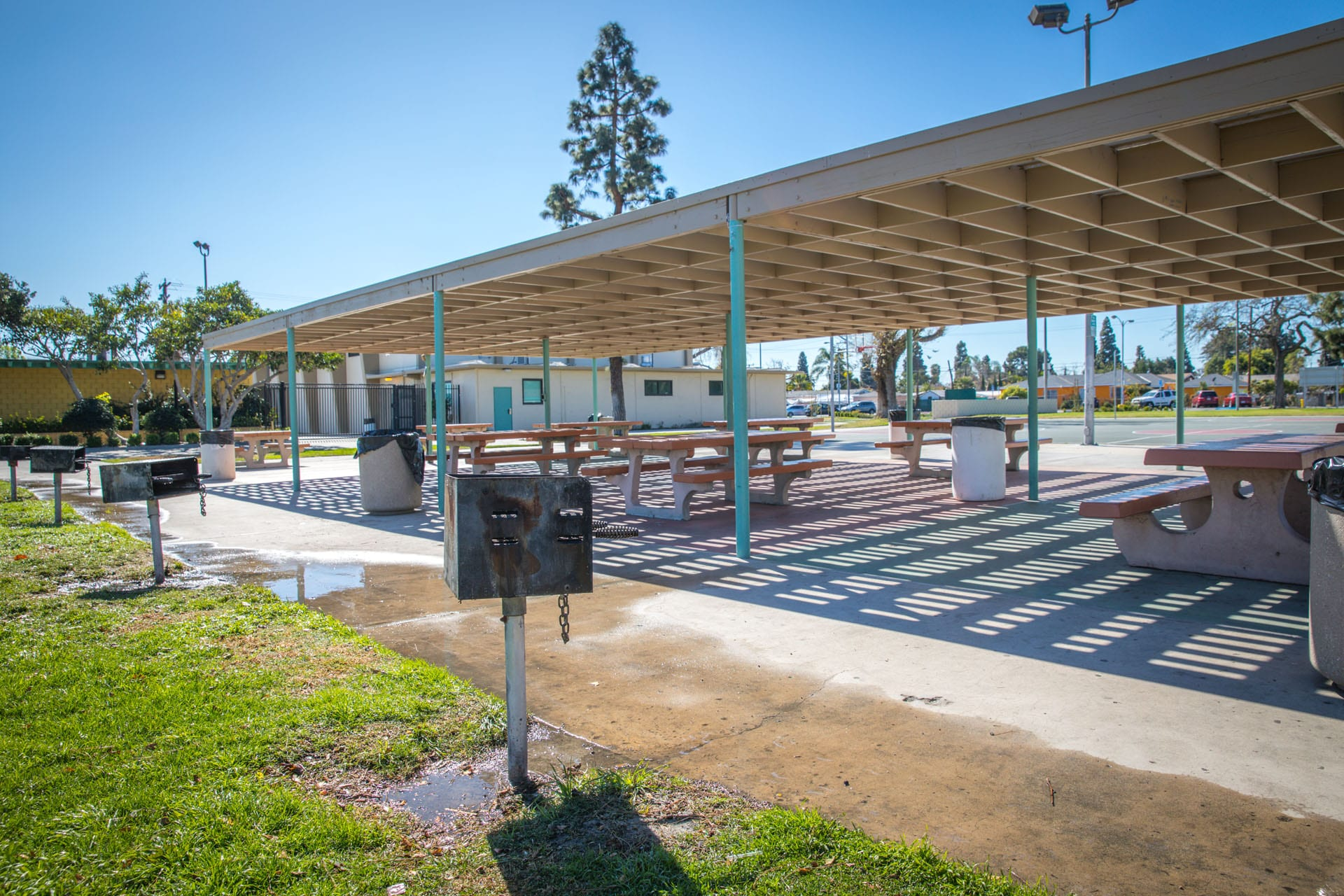 BBQ grills next to picnic tables under an awning