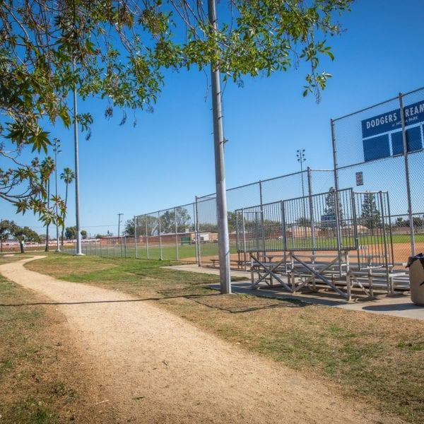 Trail running along side a baseball field