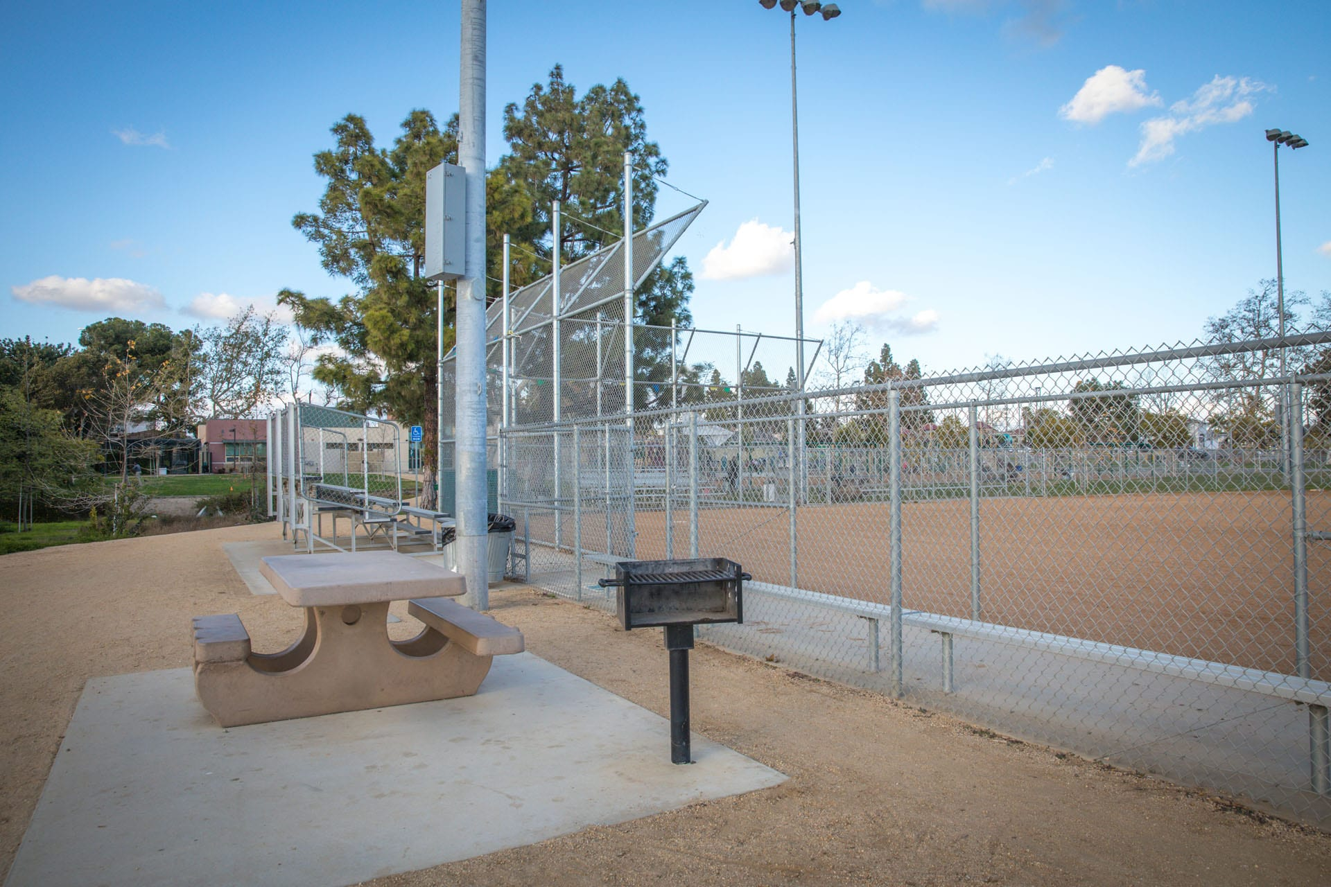 Picnic table and BBQ grill next to a baseball field