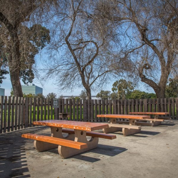Adobe picnic benches surrounded by a fence and trees