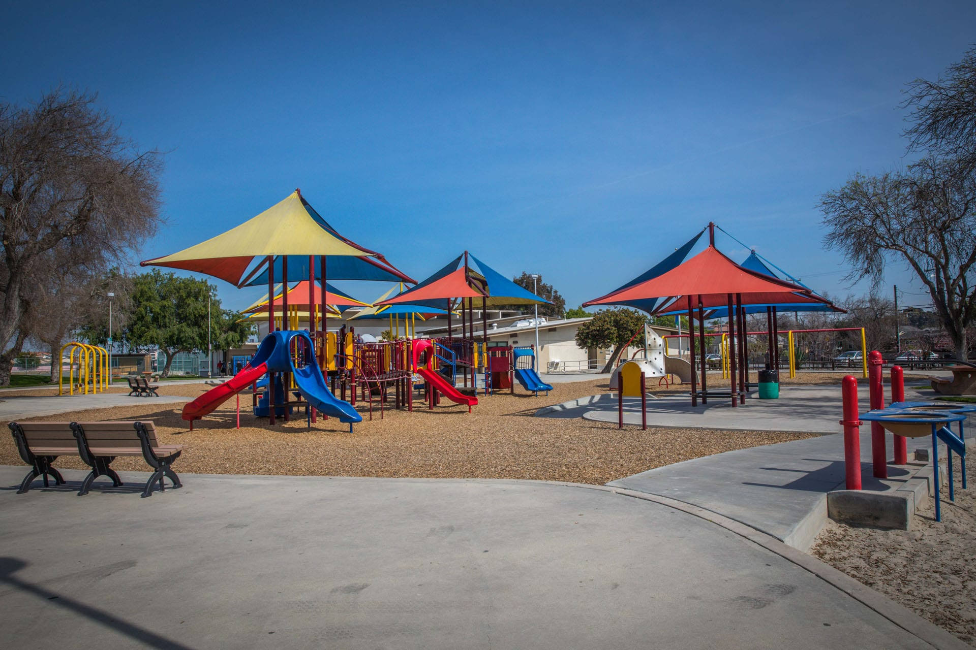 Tented playground units with benches nearby
