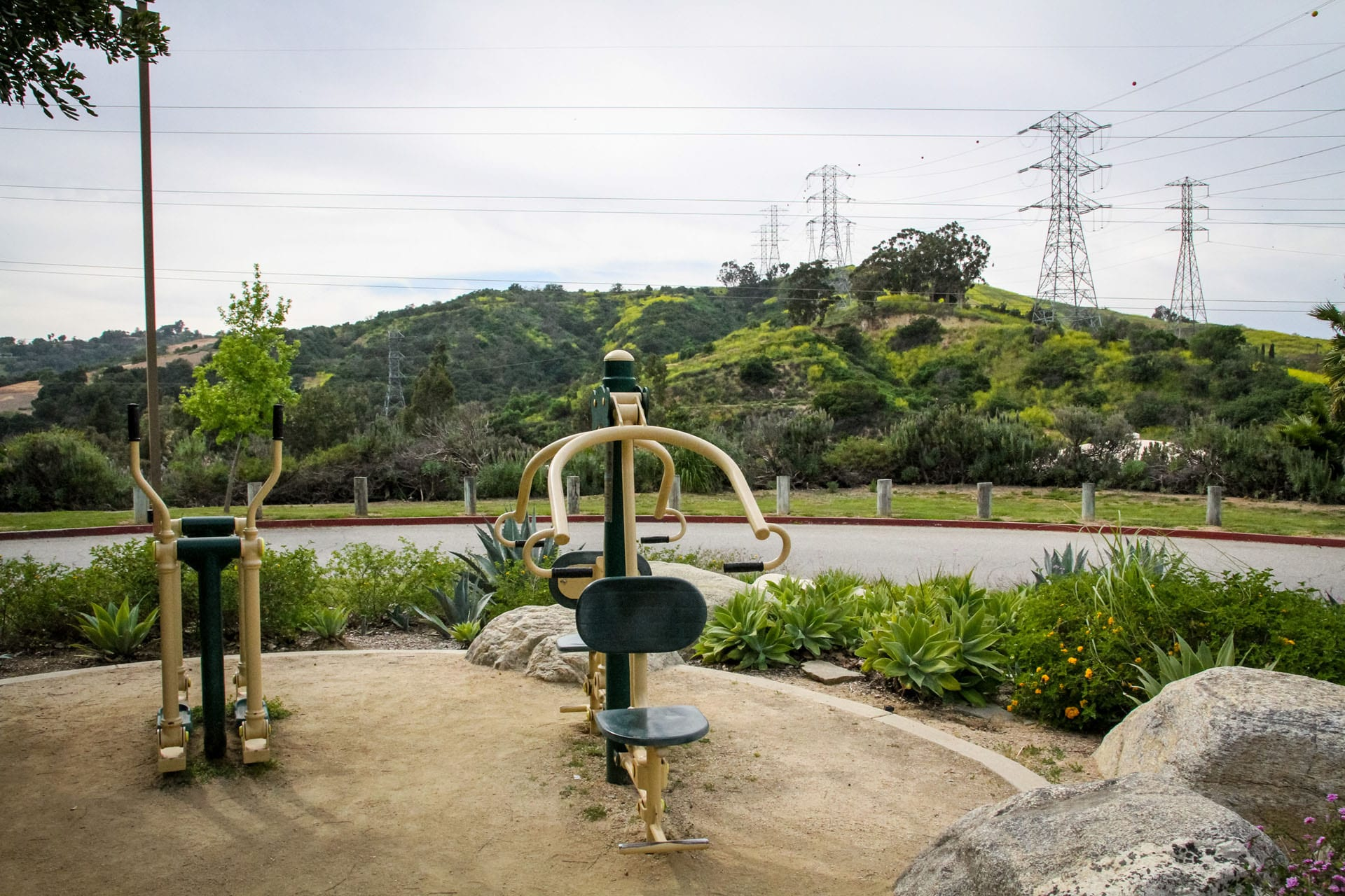 Exercise equipment over looking a walking path and green hills