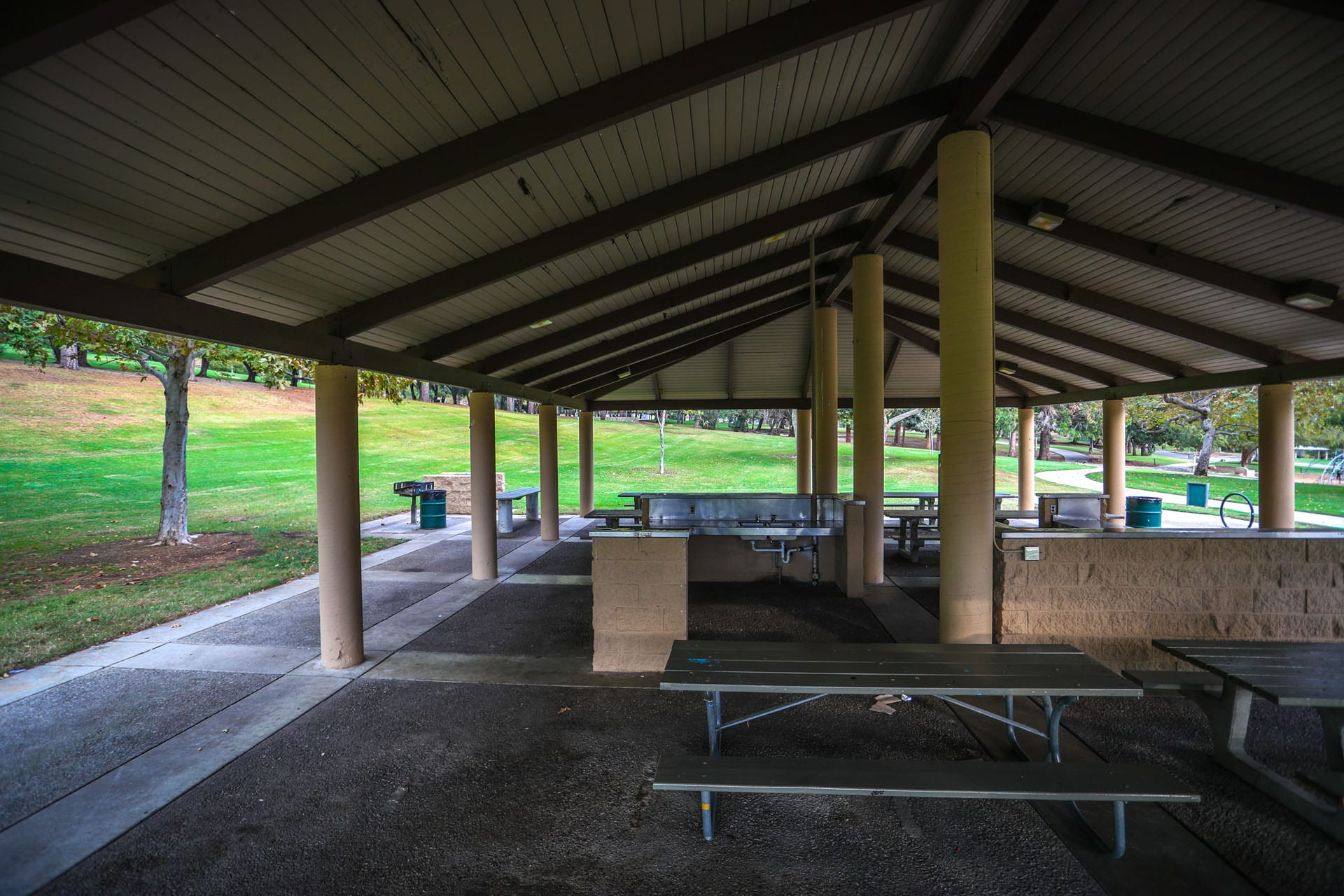 Picnic tables and kitchen area under an awning. BBQ grills just outside