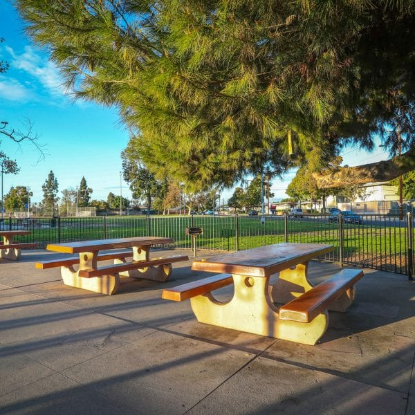 Concrete picnic tables surrounded by a fence and lawn