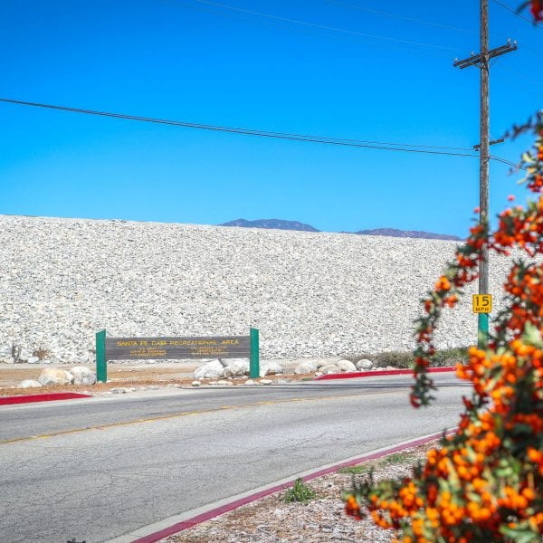 Santa Fe Dam Recreational Area sign across a road. Flowers to the right