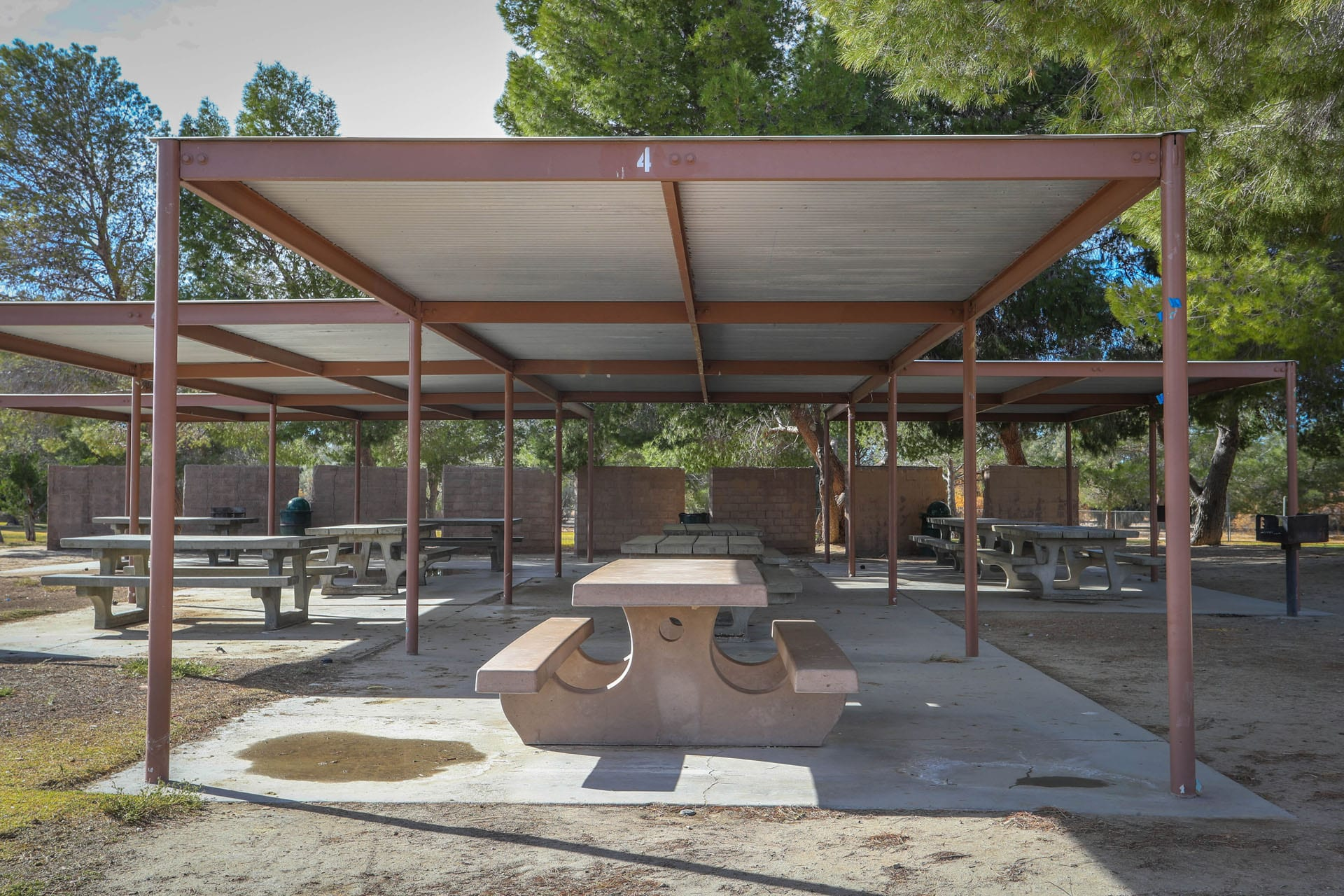 Adobe picnic tables covered by an awning