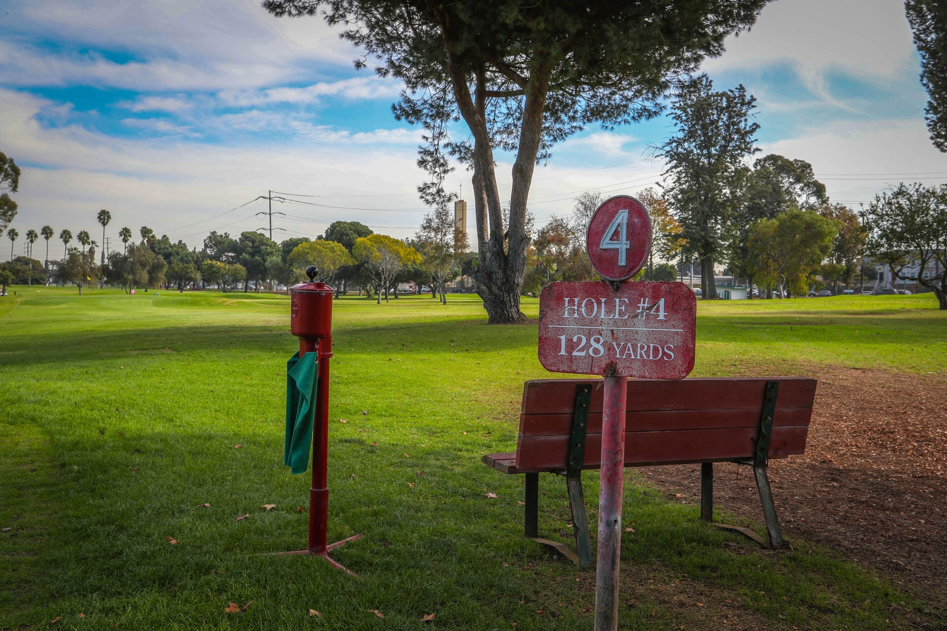 Hole #4 sign, bench, trees and green
