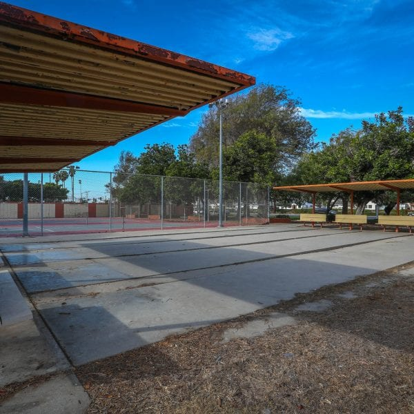 Benches under an awning and a tennis court