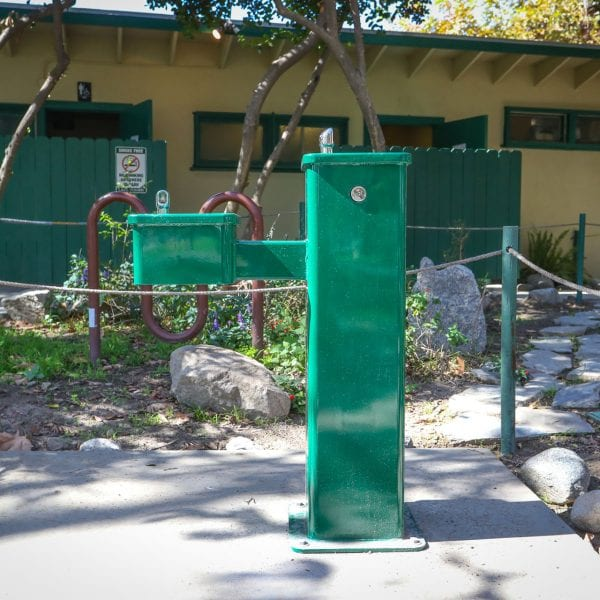 Drinking fountain, bike rack and stepping stones aside a facility