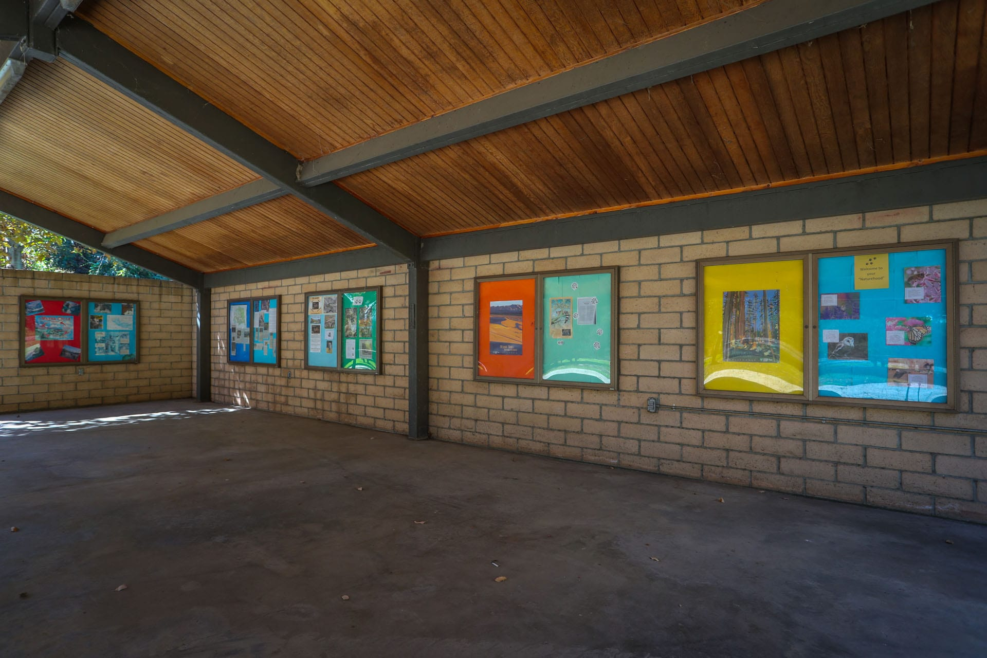 Student art in an outdoor gallery with an awning