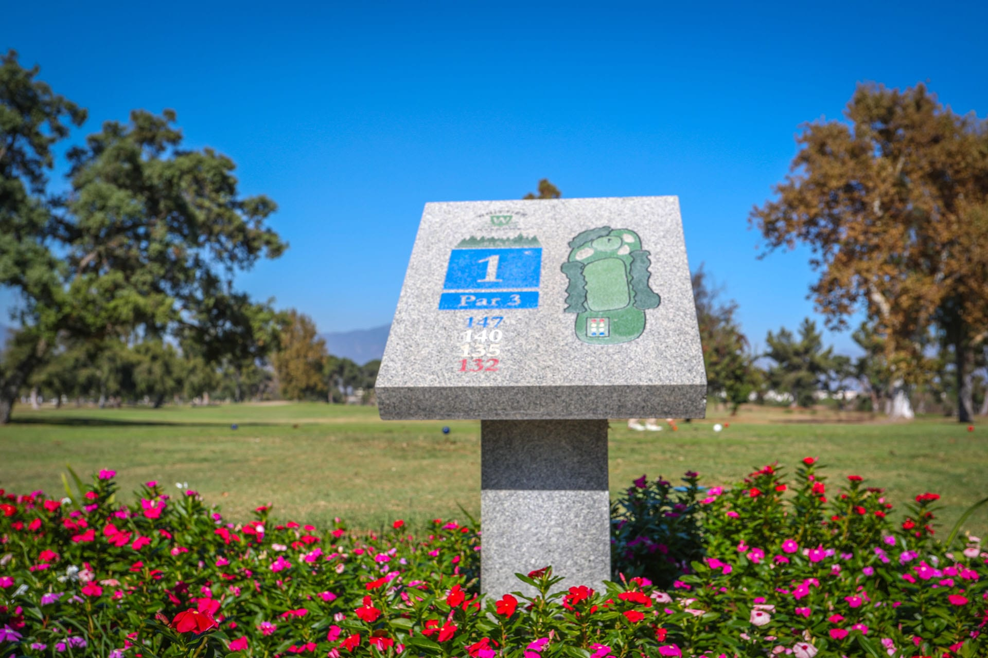 Hole 1 sign amongst flowers and golf course