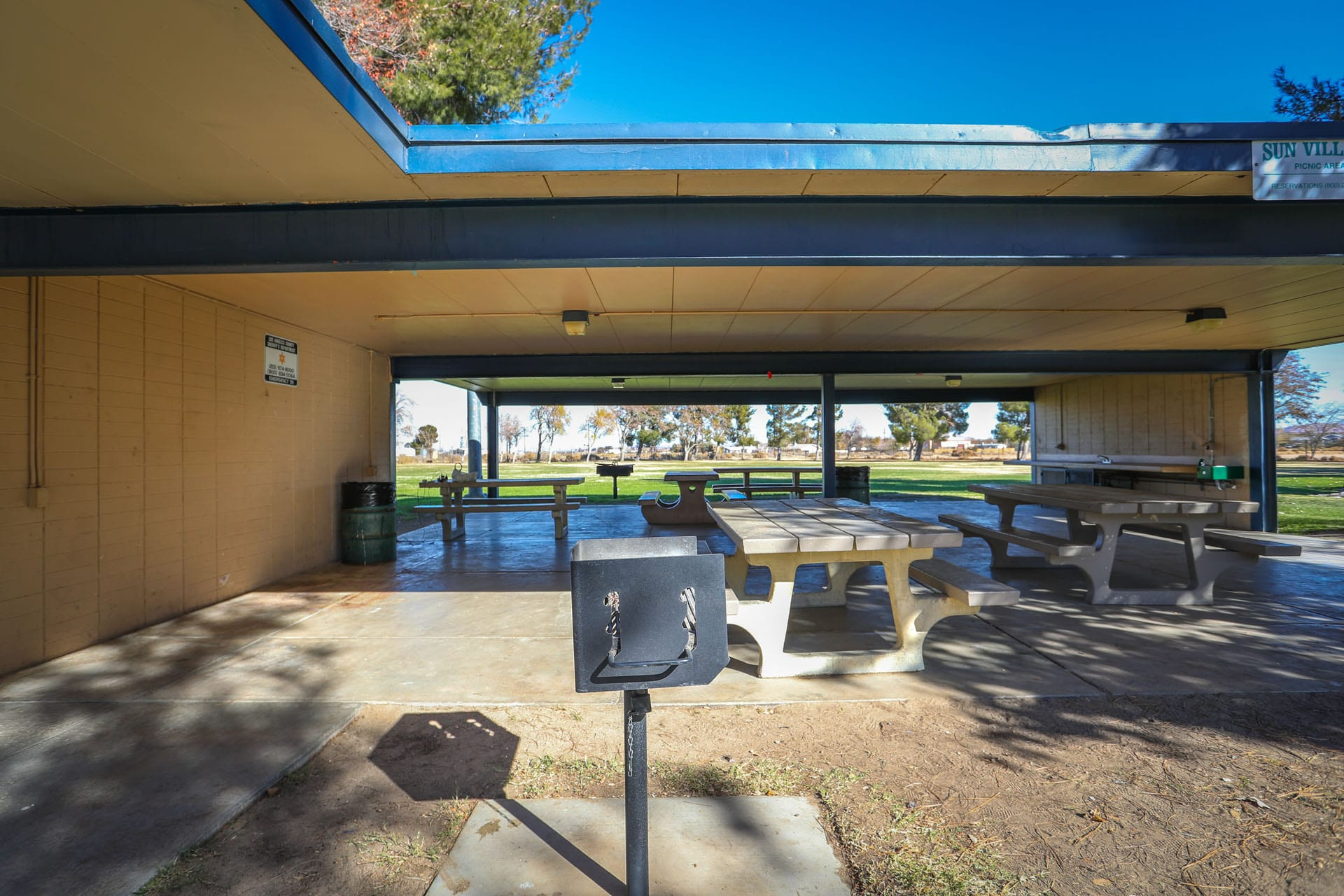 Picnic tables under and awning. BBQ grill in foreground