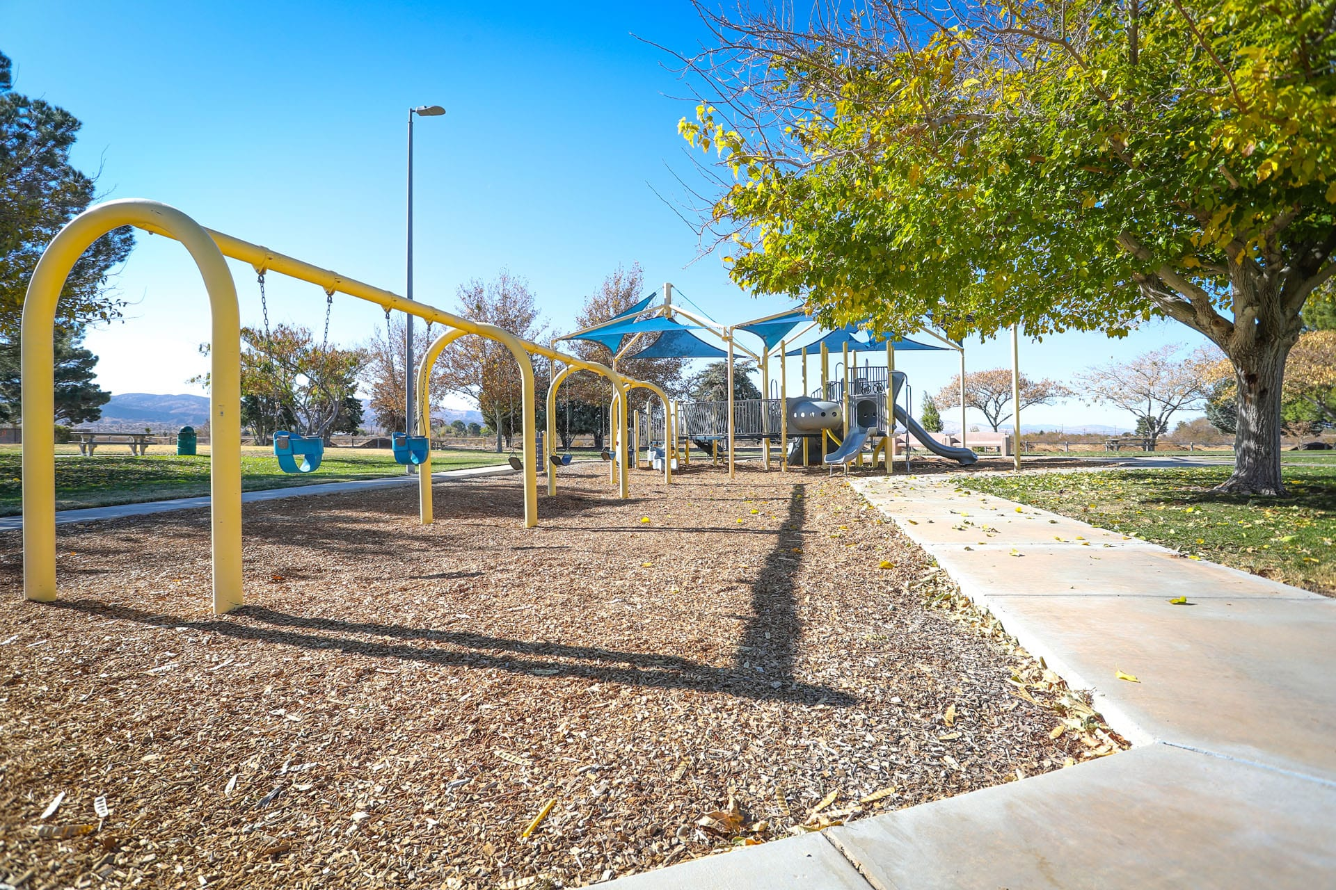 Walkway wrapping a playground and swing set