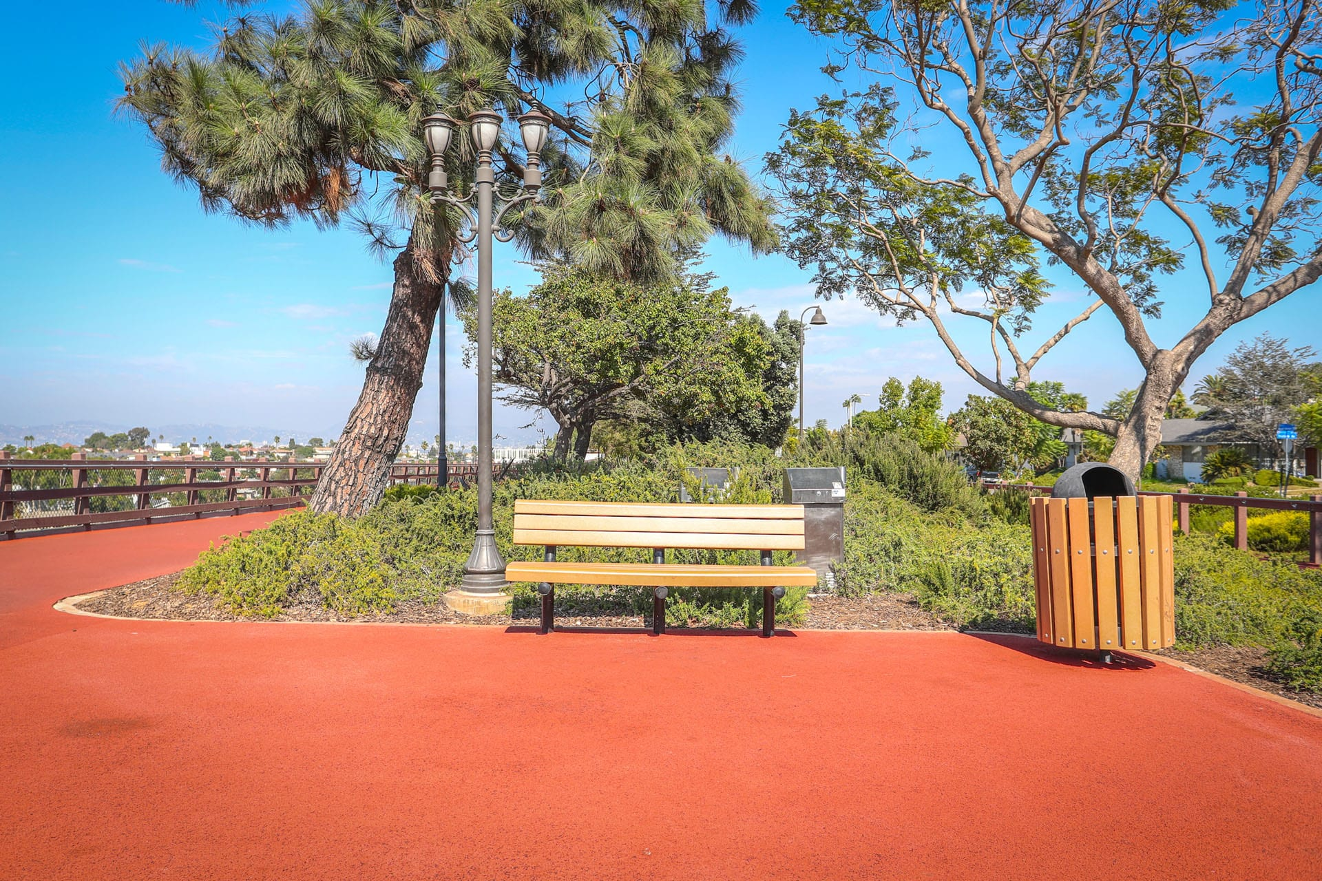 Red exercise track, bench and trash can