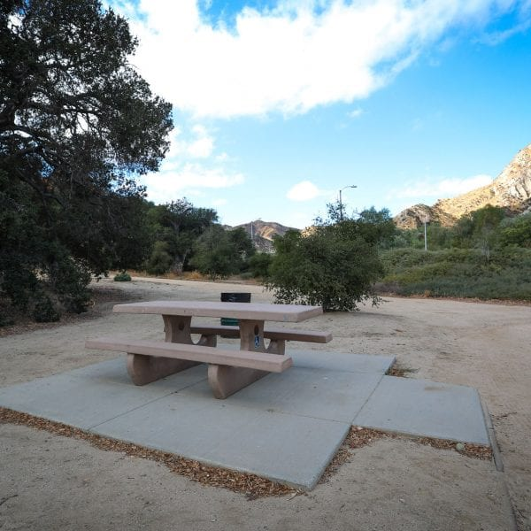 Adobe picnic table surrounded by dirt and trees