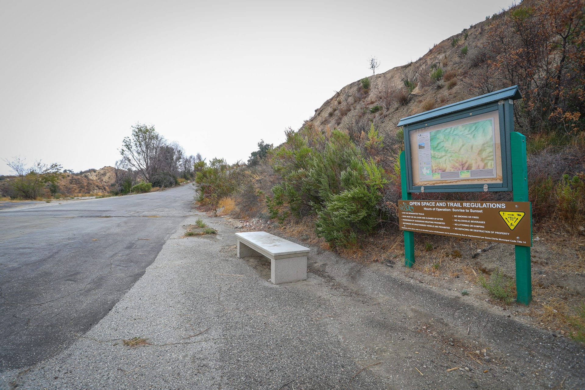 Sign and bench next to paved path